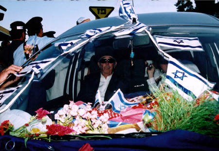 Yoseph Abbo Evron, in the decorated vehicle that brings the Torah scroll to Meron